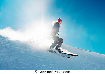 skier is riding from snow hill in the sun beam very fast
