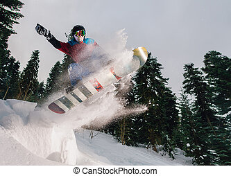 snowboarder is jumping very high and freeriding from hill in...