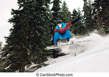 snowboarder is jumping and freeriding in the mountain forest...