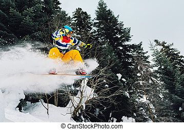 snowboarder is jumping and freeridingin the mountain forest...