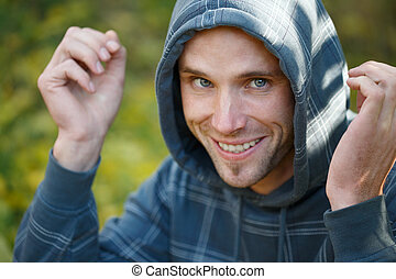 Young beautiful smiling man in sports wear and hood on head...