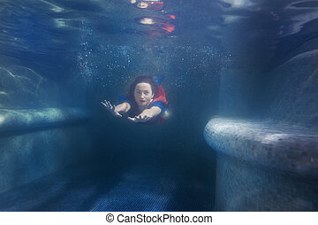 Woman swims under the water like a mermaid. - Woman swims...