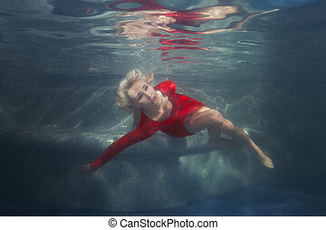 Woman blonde under the water in the pool. - Blond woman...