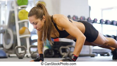 Well trained woman doing push ups at exercise mat in the gym...