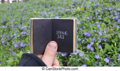 Spring sale idea, book with text and spring field with blue...