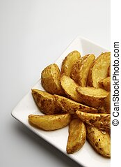 fried potato wedges - forefront of a fried potato slices on...