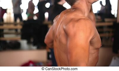 Sideview of a male bodybuilder with bare torso doing...