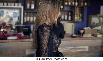Couple at a cafe. A beautiful girl goes to a meeting with a...