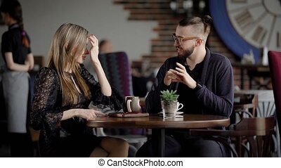 Business people at lunch break in a cafe. Two men and a woman talk about work during lunch. Beautiful young people, designers or managers communicate on working subjects.