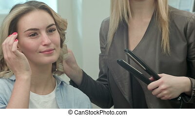 Hairdresser is making the hairstyle, curls of hair strands...