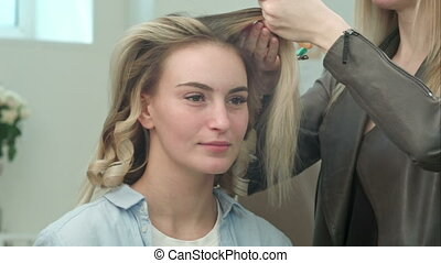Professional hair stylist doing hairstyle of beautiful blond...