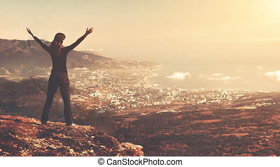 Young woman stand on top of mountain with raised hands in...