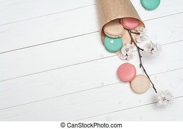 Package with colored macaroons and flowers on a white wooden background