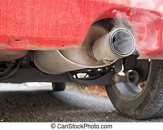 Diesel exhaust, old red car. Detail. With smoke.