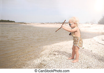 Toddler Girl Playing on Beach Throwing Sticks in the Water -...