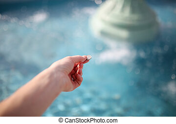 Woman's Hand Throwing Coin in Wishing Fountain