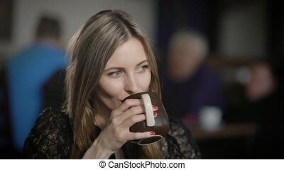 Portrait of a beautiful young woman in a cafe. She drinks...