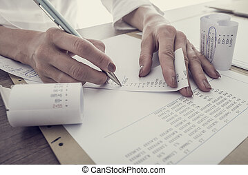 Retro toned image of accountant summing up the numbers