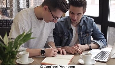 Young freelancers using notebook in the cafe for his work or...