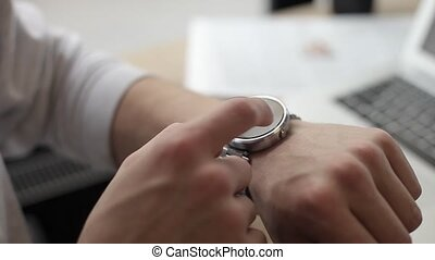 Young man using smart watch sitting in cafe - Young man...