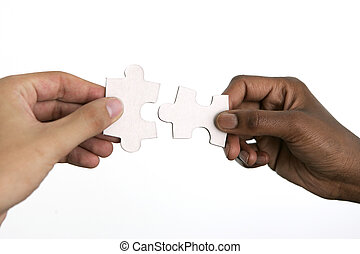 Hands trying to fit two puzzle pieces together, on white...
