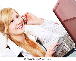 smiling blond woman working with computer and talking by...