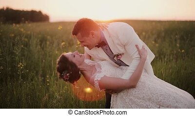 Handsome groom holds his beautiful bride in his arms,...