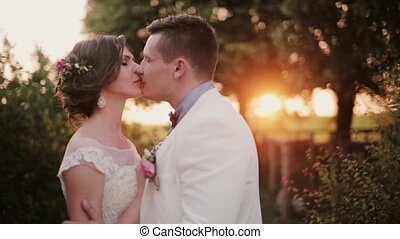 Happy lovers kiss at sunset on their wedding day. Beautiful view of lovers in nature, sunset rays of light.