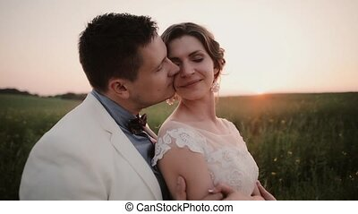 Handsome groom hugging his beautiful bride in a field at sunset on wedding day. Beautiful nature in summertime.