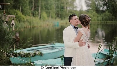 Beautiful lovers kiss near a pond with blue boats on it in a...