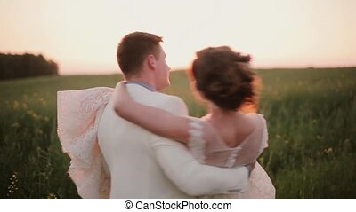 Handsome groom holds his beautiful bride in his arms and swirls around. She laughs and kisses him. Sunset in nature