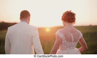 Back view of lovers walking in a field at sunset, happily...