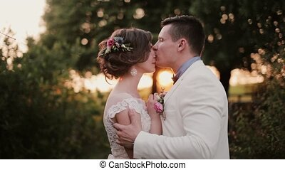 Happy lovers kiss at sunset in very picturesque place on wedding day. Beautiful view of lovers in nature. Side view