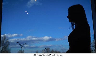 Silhouette of a slender woman against the window. The...