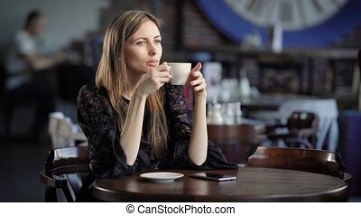 Portrait of a beautiful woman in a cafe or restaurant. A girl drinks tea or coffee and dreams about something.