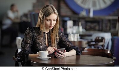 young cute woman using phone ,sitting at a cafe holding a...