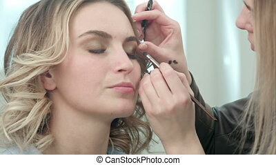 Make-up artist applying eyelash makeup to model eye