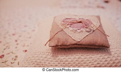 Two wedding rings on a little pillow. Preparation for a ceremony, details of wedding in rustic style. Slider right.