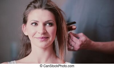 Portrait of young attractive woman preparing in the morning. Hairdresser do a new hairstyle for a girl.
