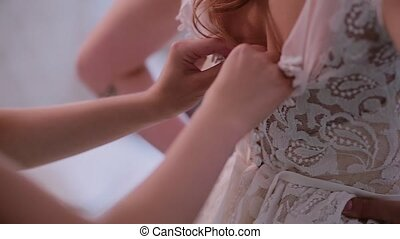 Close-up view of bridesmaid hands helping to put on the wedding dress. Morning preparation of young bride with tattoo.