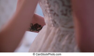 Bridesmaid helping to put on the wedding dress, buttons the...