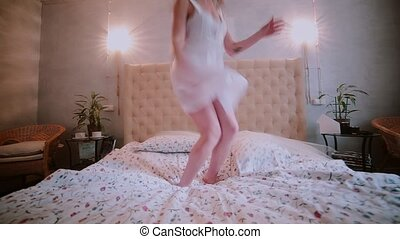Happy fresh brunette woman in night dress jumping on bed,...