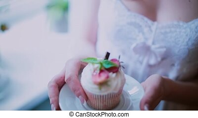 Close-up view of beautiful cupcake on a saucer. Woman holds...