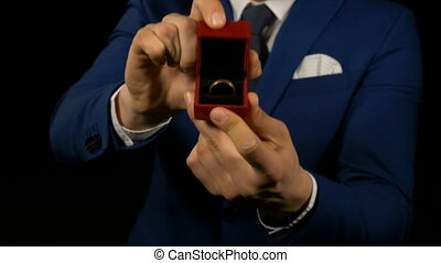 Hands of young man opening ring box with wedding ring inside...