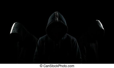 Faceless mysterious hooded individuals