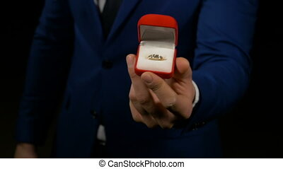 Business man proposing and showing engagement ring box