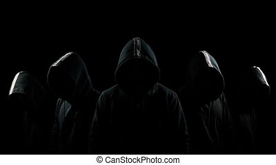 Five mysterious hooded men standing in the dark
