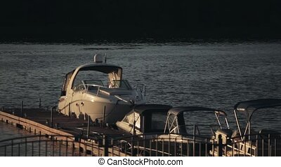 Wooden pier in the evening sunset. Motor boat standing near...