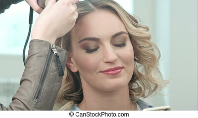 Young pretty woman use smartphone in beauty salon, while...