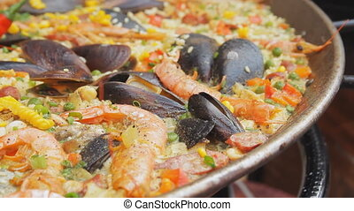 Spanish paella with yellow rice, shrimps and mussels cooking at the food market. Street food festival. Rice with seafood boiling close up. Traditional spanish food.